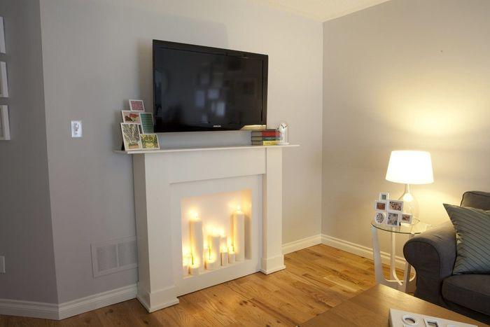 Идея дизайна интерьера гостиной - декоративный камин со свечами.